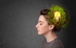 Barnet är besvärad att tänka av grön ecoenergi med lightbulben Royaltyfria Bilder
