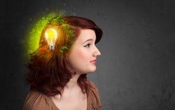 Barnet är besvärad att tänka av grön ecoenergi med lightbulben Arkivfoton