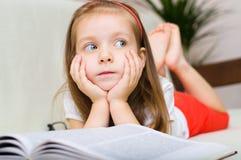 Barnet är läseboken, medan ligga på en soffa Royaltyfria Foton