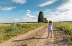 Barnet är på en lantlig väg till byn arkivbilder
