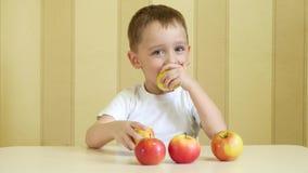 Barnet äter och spelar med röda och gröna äpplen, sitter på tabellen och visar tummen av nöje och språket lager videofilmer