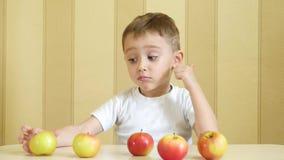 Barnet äter och spelar med röda och gröna äpplen som sitter på tabellen och visar tummen av nöje lager videofilmer
