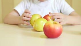 Barnet äter och spelar med rött, och gröna äpplen, sitter på tabellen Fokusen av kameran flyttar sig från framsidan till arkivfilmer