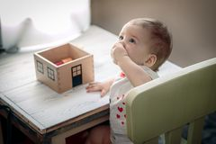 Barnet äter på tabellen Leksakhus på tabellen royaltyfri bild