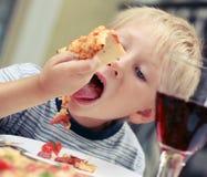 Barnet äter pizza i cafeÑŽ Royaltyfria Bilder