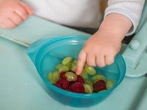 Barnet äter raspberreis Arkivbilder