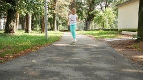 Barnet åker skridskor skilfully i parkera 7-8 år gammal flicka på en skateboard långsam rörelse arkivfilmer