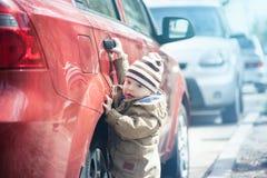 Barnet öppnar den röda bilen royaltyfri fotografi