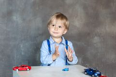 Barnet appl?derar hans h?nder Stående av en gullig pys som spelar med bilar Förskole- pojke som spelar med leksakbilar i dagis E royaltyfri fotografi