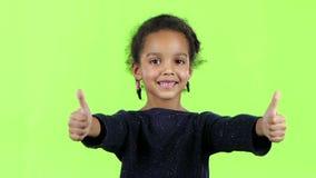 Barnet av en afrikansk amerikan visar upp tummar grön skärm långsam rörelse lager videofilmer