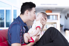 Barnet avlar att kyssa som är hans, behandla som ett barn på soffan Royaltyfria Bilder