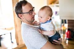Barnet avlar att rymma hans gulligt behandla som ett barn sonen i armarna Fotografering för Bildbyråer