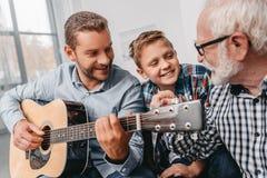 Barnet avlar att spela gitarren, medan den lilla sonen och farfadern är royaltyfria bilder
