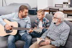 Barnet avlar att spela gitarren, medan den lilla sonen och farfadern är royaltyfria foton