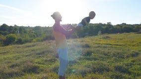 Barnet avlar att spela med hans barn på naturen Farsan som rymmer hans son` s, lägger benen på ryggen och kastar den som är utomh Arkivfoto