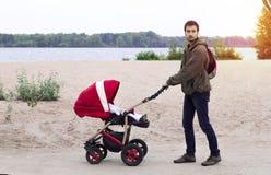 Barnet avlar hjälp moder, honom går med en barnvagn i Royaltyfria Foton