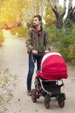 Barnet avlar hjälp moder, honom går med en barnvagn i Royaltyfri Fotografi