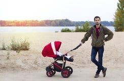 Barnet avlar hjälp moder, honom går med en barnvagn i Arkivfoton