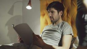 Barnet avlar läseboken medan hans lilla sonbanhoppning på säng, innan de sover i afton lager videofilmer