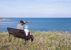 Barnet avlar med barnsammanträde på bänken nära havshavet Royaltyfri Fotografi