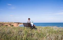 Barnet avlar med barnsammanträde på bänken nära havshavet royaltyfri bild