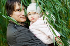 Barnet avlar med den lilla dottern på bakgrund av det gröna trädet Arkivbilder