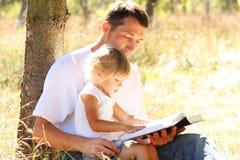 Barnet avlar med hans lilla dotter läser bibeln Arkivbild