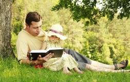 Barnet avlar med hans lilla dotter läser bibeln royaltyfria foton