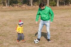 Barnet avlar med hans lilla son som spelar fotboll, fotboll i parkera Royaltyfria Bilder