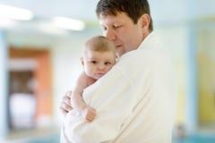 Barnet avlar, och hans lilla gulliga nyfött behandla som ett barn dottern tillsammans i brunnsorthotell Arkivbilder