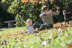 Barnet avlar och hans litet barnbarnsammanträde i ett höstgräs pl Arkivbild