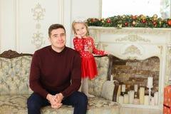 Barnet avlar sammanträde med den lilla dottern på dekorerade spisen för soffan den nära Royaltyfria Foton