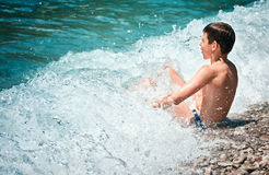 Barnet badar den Lustica för det vågbränningAdriatik havet stranden Zanjic Montenegro Fotografering för Bildbyråer
