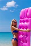 Barnet bantar den blonda kvinnan i solglasögon på den tropiska stranden fotografering för bildbyråer