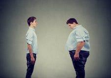 Barnet bantar den färdiga mannen som ser fett själv Banta den sunda livsstilen för prima höger näring arkivbild