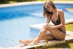 Barnet bantar den härliga kvinnan i bikinin som applicerar olja Royaltyfria Foton