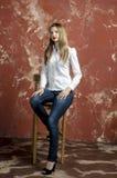 Barnet bantar den härliga unga blonda kvinnan med långt ben och hår i tumultskjorta och jeans Royaltyfria Foton