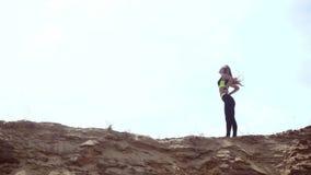 Barnet bantar den idrotts- blondinen i sportlikformign som poserar på en sandkulle arkivfilmer