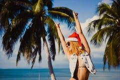 Barnet bantar den röda hatten för den sexiga flickan av Santa Claus på julsmartphonen Arkivfoto