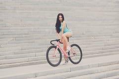 Barnet bantar den sexiga sportive kvinnan på cykeln Arkivbild