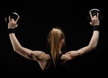 Barnet bantar den starka muskulösa kvinnan som poserar i studio med hanteln Arkivfoto