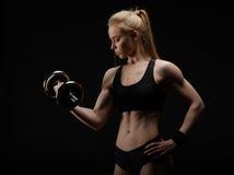 Barnet bantar den starka muskulösa kvinnan som poserar i studio med hanteln Arkivfoton