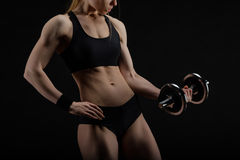 Barnet bantar den starka muskulösa kvinnan som poserar i studio med hanteln Royaltyfri Fotografi