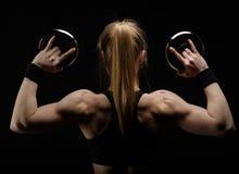 Barnet bantar den starka muskulösa kvinnan som poserar i studio med hanteln Royaltyfria Bilder