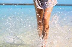 Barnet bantar färdiga färgstänk för kvinnadanandevatten med hennes ben Semester- och sommarlynne Arkivfoto
