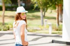 Barnet bantar kvinnan i den vita hatten som står utomhus- Royaltyfria Bilder