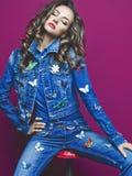 Barnet bantar kvinnan i jeans med många broscher Royaltyfria Foton