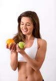 Barnet bantar kvinnan i sportar bästa hållande apelsin och äpple Arkivfoton