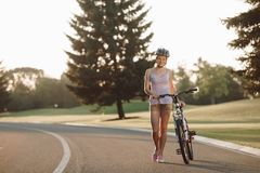 Barnet bantar kvinnan med cykeln utomhus Fotografering för Bildbyråer