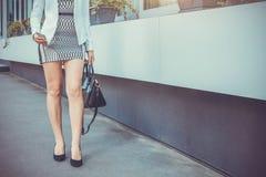 Barnet bantar kvinnan som går av gatan som bär höga häl Royaltyfria Bilder